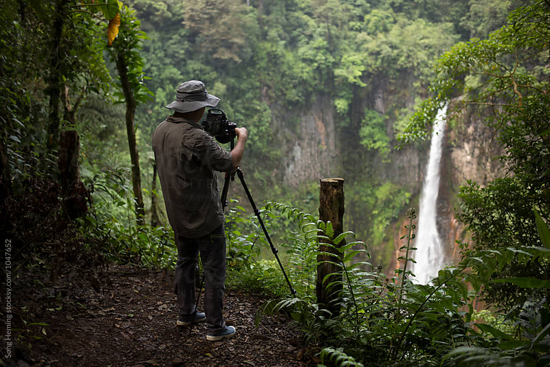 A man take photo for the waterfall in the rain forest by Song Heming for Stocksy United