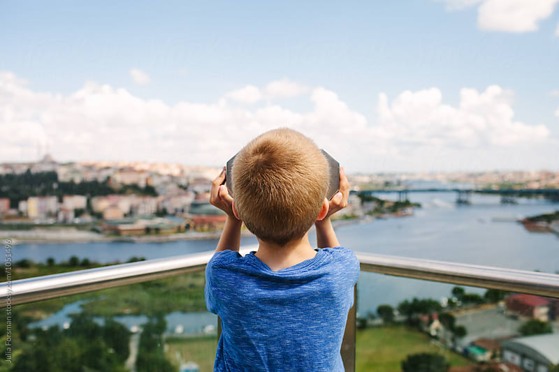 Sightseeing child looks through fixed binoculars towards an out of focus view. by Julia Forsman for Stocksy United