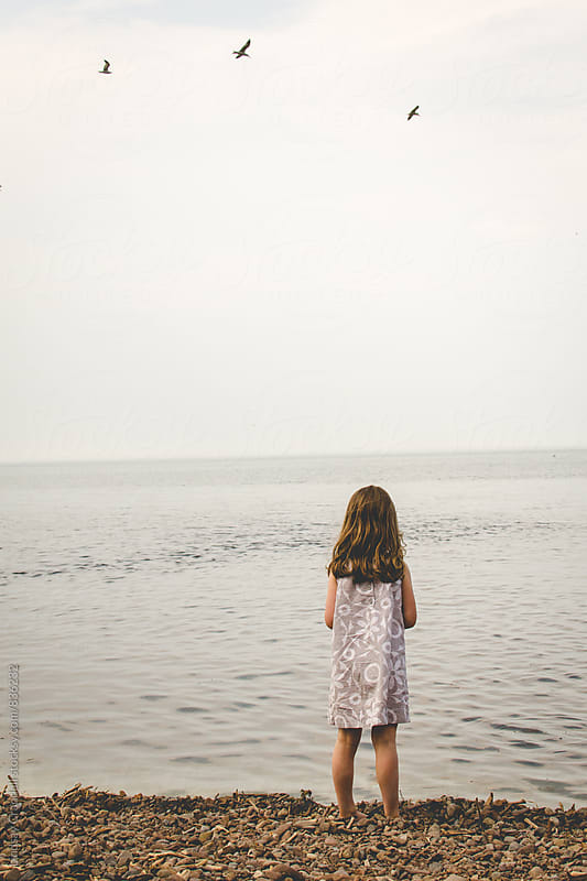 Child standing on stone beach by the sea by Lindsay Crandall for Stocksy United