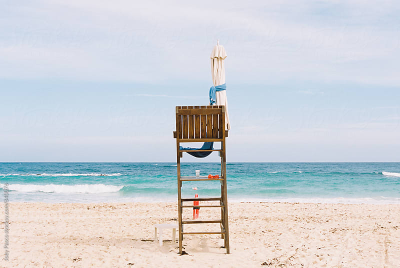 Empty lifeguard chair on white sand Caribbean beach by Joey Pasco for Stocksy United