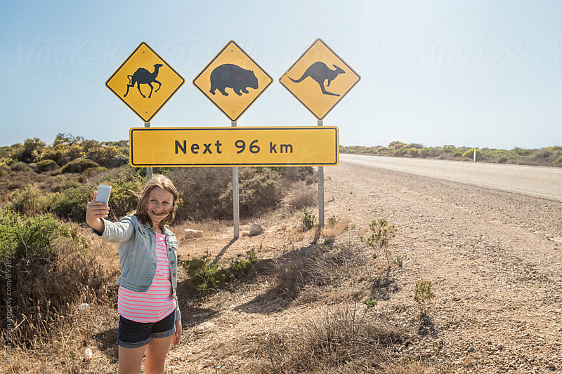 teen girl taking a selfie in front of an animal warning road sign in Australia by Gillian Vann for Stocksy United