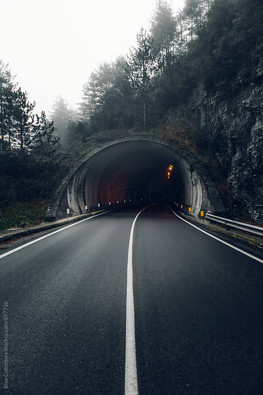 Foggy road view before the tunnel by Jordi Rulló for Stocksy United