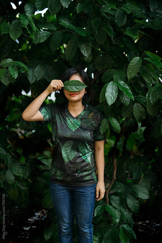 A woman covers her eyes with a leaf by Alita Ong for Stocksy United