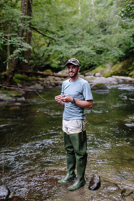 Man smiling and fly-fishing in clear river trying to catch fish by Matthew Spaulding for Stocksy United