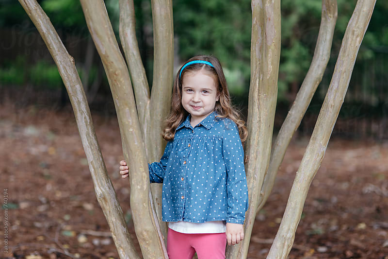 Beautiful young girl standing in a tree by Jakob for Stocksy United