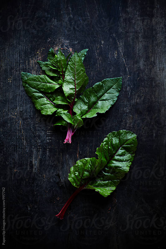 Chard leaves on dark wooden background by Paperclip Images for Stocksy United