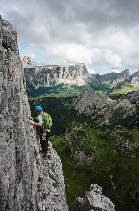 Female alpinist walking along a narrow ledge, rock climbing outdoor by RG&B Images for Stocksy United