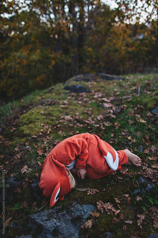 Child in fox costume pretend sleeping outside by Rob and Julia Campbell for Stocksy United