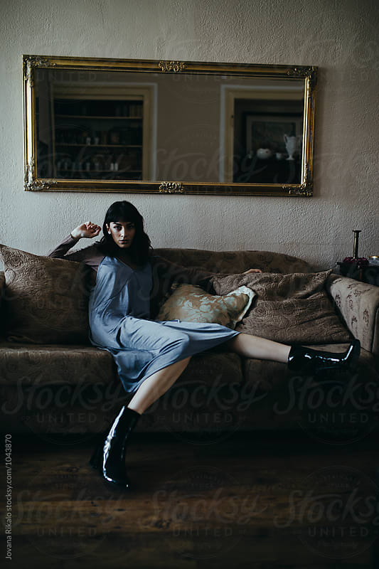 Fashionable woman sitting on sofa by Jovana Rikalo for Stocksy United