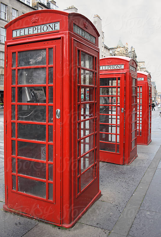 Three typical English phone boxes in a row by Melanie Kintz for Stocksy United
