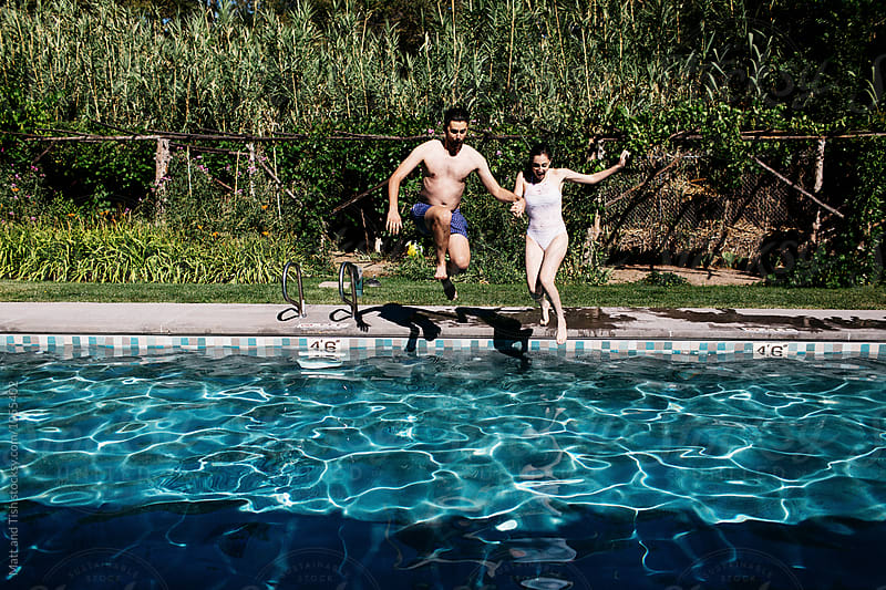 Man and woman jumping in pool by Matt and Tish for Stocksy United
