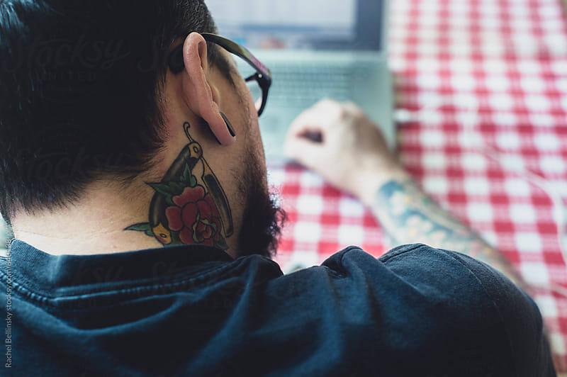 A handsome tattoo'd man in window light by Rachel Bellinsky for Stocksy United