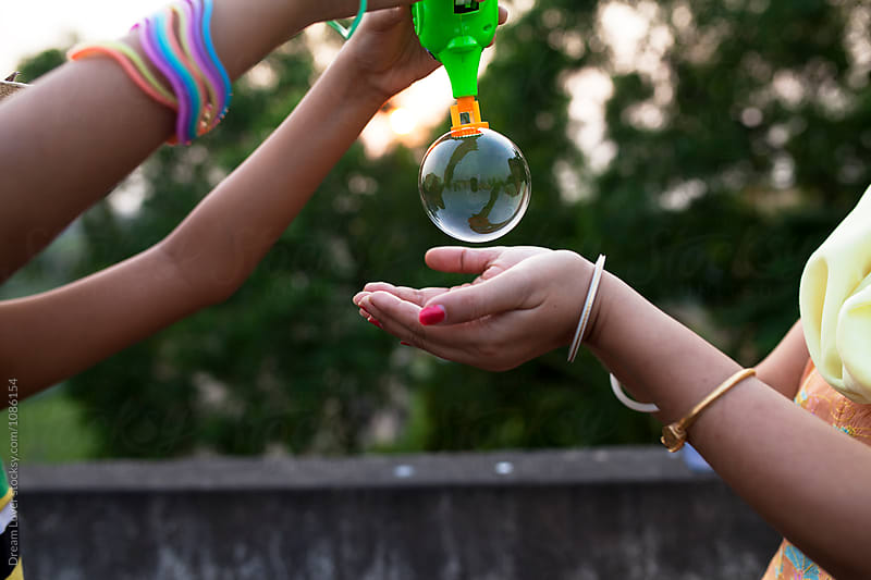 Mother and daughter making fun with bubbles by PARTHA PAL for Stocksy United