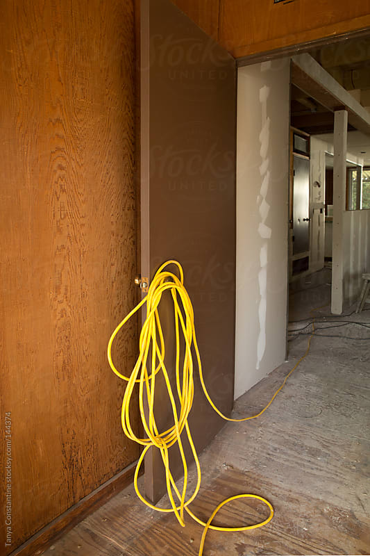 yellow cord hanging on door knob at construction site by Tanya Constantine for Stocksy United