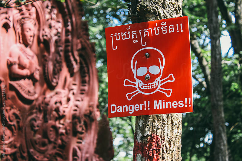 Danger mines sign and a skull design on dangerous mined area by Alejandro Moreno de Carlos for Stocksy United