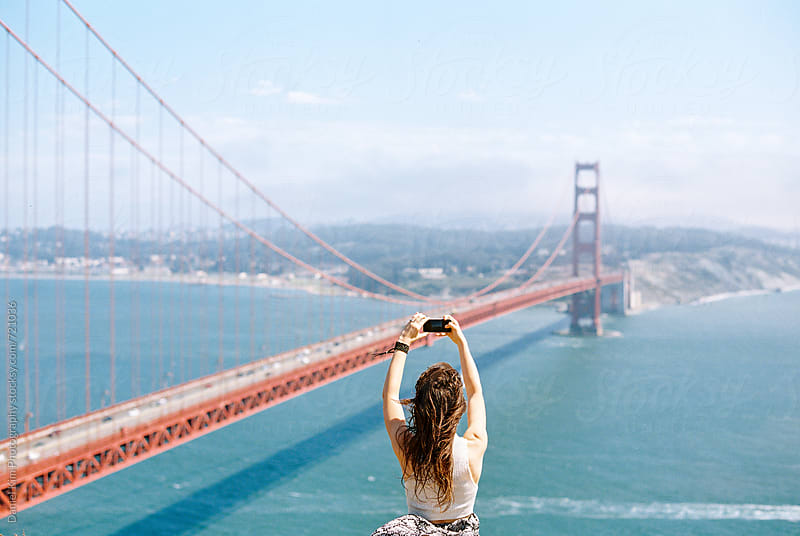 Woman taking picture of Golden Gate Bridge by Daniel Kim Photography for Stocksy United