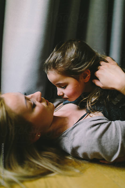 Mother embracing her daughter laying on the floor by Evgenij Yulkin for Stocksy United