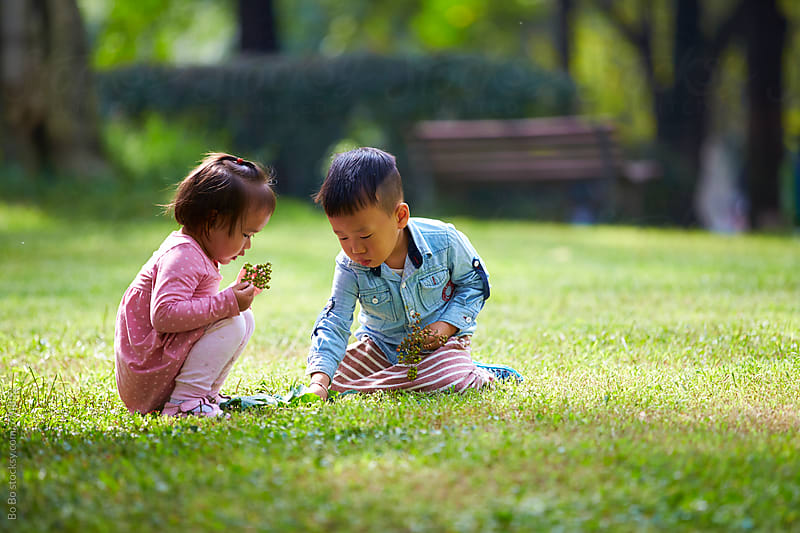 two lovely asian kids together in the park by Bo Bo for Stocksy United