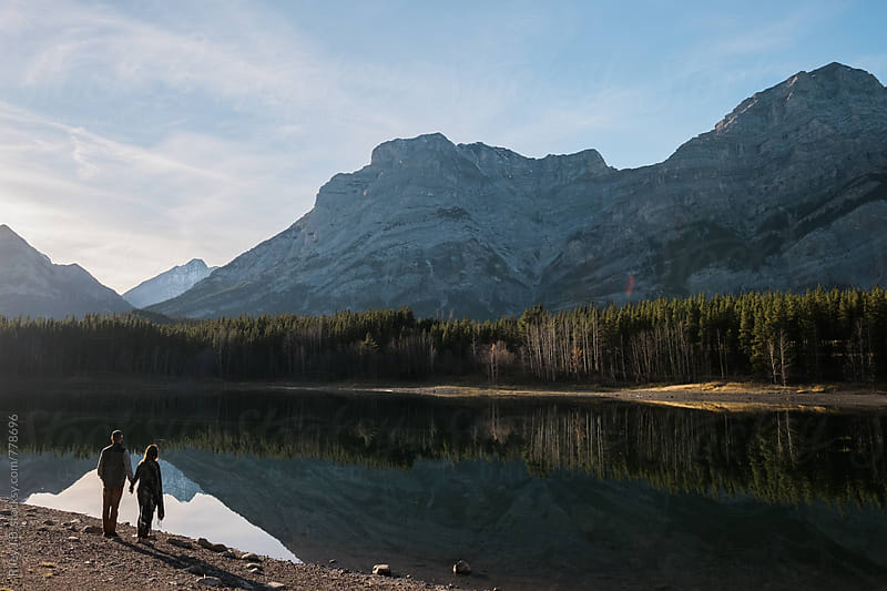 A young man & woman stand holding hands framed by a mountain reflection in a pond by Riley Joseph for Stocksy United