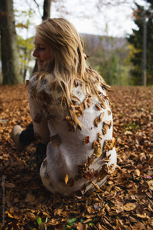 Young woman sitting on a bed of dry leaves by michela ravasio for Stocksy United