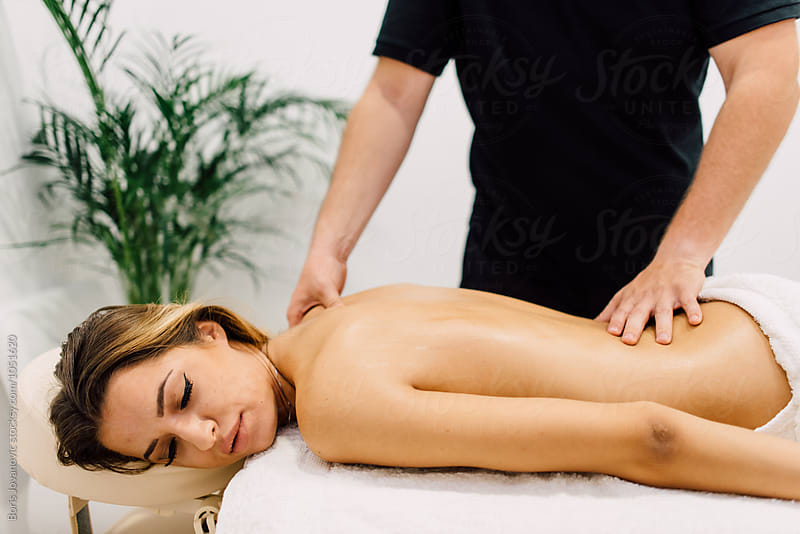 Woman enjoying massage treatment indoor by Boris Jovanovic for Stocksy United