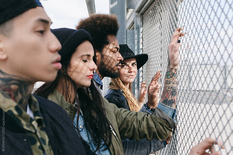 Group of friends standing through a fence. by BONNINSTUDIO for Stocksy United