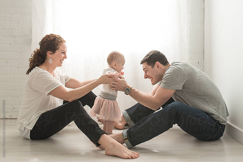 Parents Help Their Baby Girl Learn To Walk by Alison Winterroth for Stocksy United