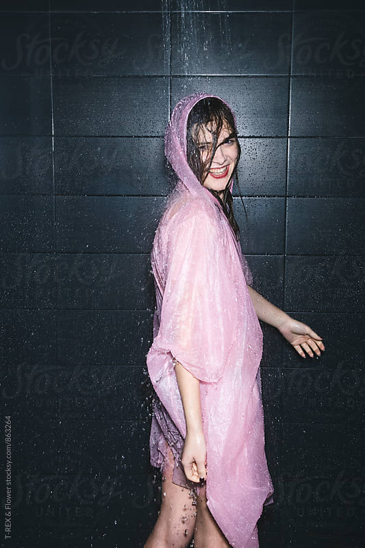 Side view of smiling young woman in pink raincoat taking a shower by T-REX & Flower for Stocksy United