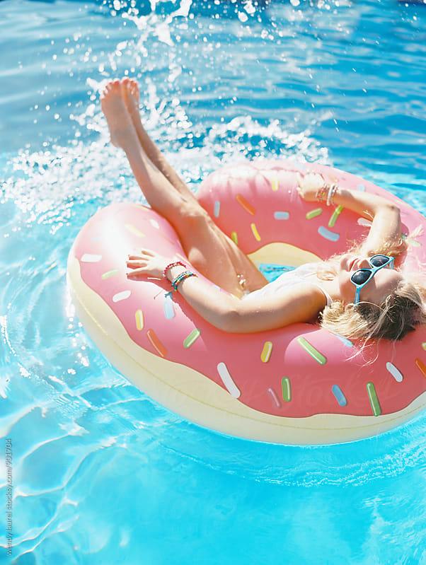 blonde girl in donut floatie in swimming pool splashing by wendy laurel for Stocksy United