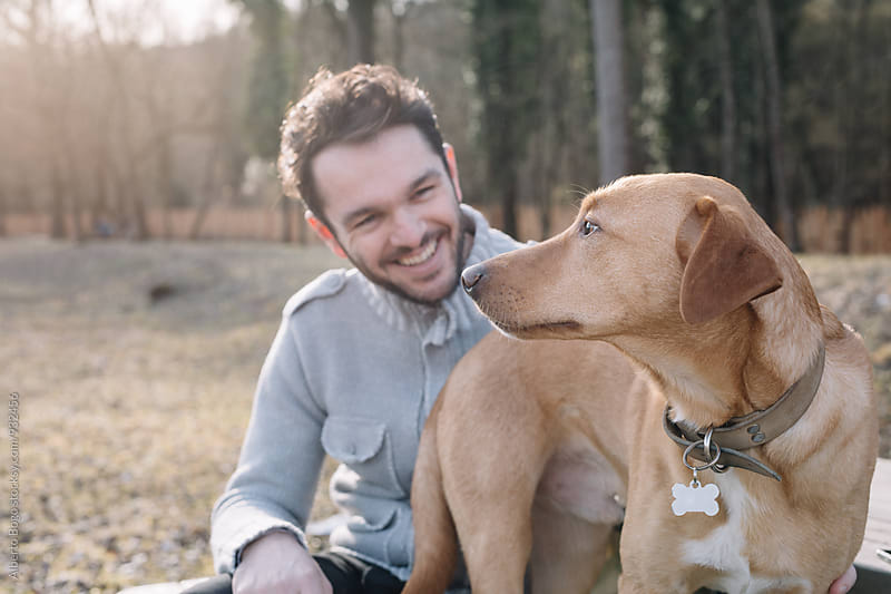 Bearded man looking at his cute dog by Alberto Bogo for Stocksy United