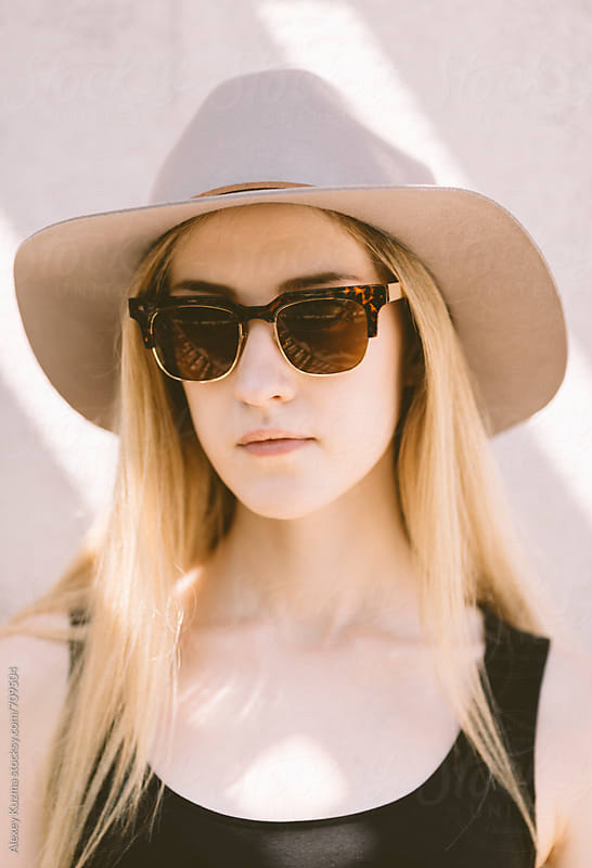 real young woman with vintage sunglasses and grey hat  by Alexey Kuzma for Stocksy United