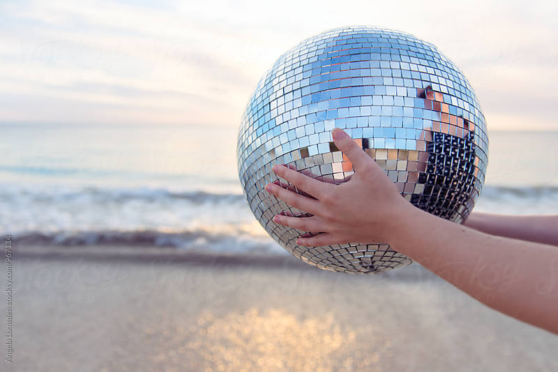 A large mirrored disco ball held out at the beach at sunset by Angela Lumsden for Stocksy United