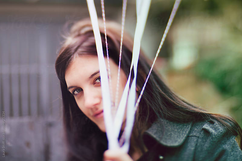 Blurred portrait of a brunette girl hiding behind white ribbons while looking at the camera in garden by Laura Stolfi for Stocksy United