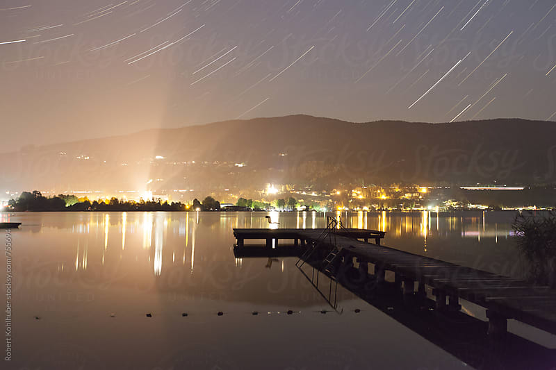 Startrails at a small dock in Mondsee, austria at night by Robert Kohlhuber for Stocksy United
