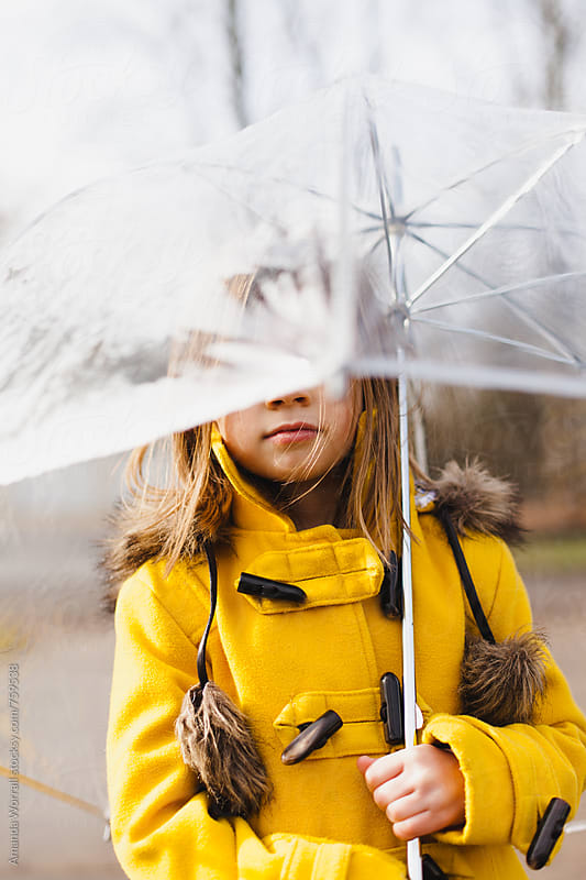 Girl wearing yellow gold duffle coat is holding a clear umbrella by Amanda Worrall for Stocksy United