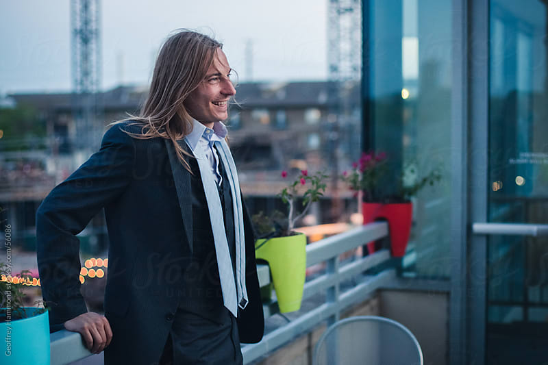 Young Businessman Smiling on Rooftop by Geoffrey Hammond for Stocksy United