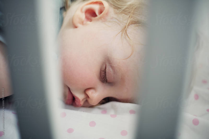 Baby asleep in a cot by sally anscombe for Stocksy United