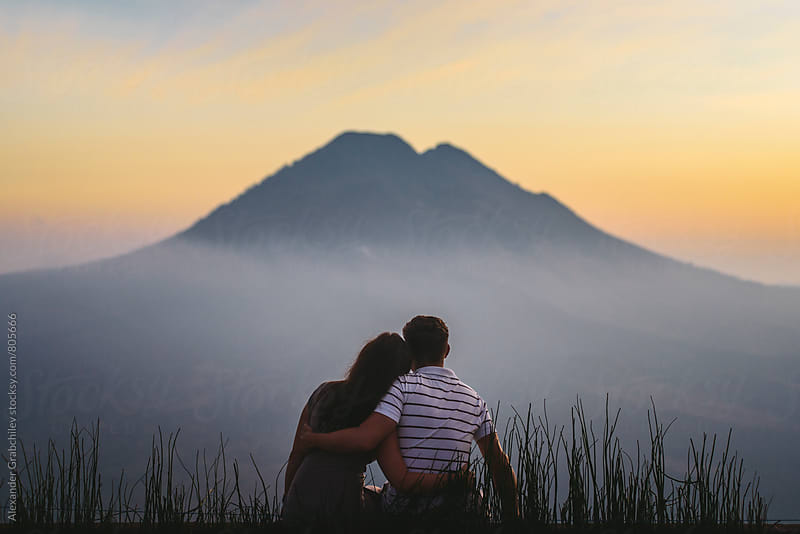 young couple watching sunrise in mountains by Alexander Grabchilev for Stocksy United