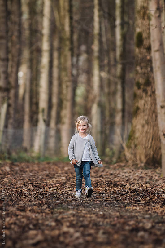 trendy cute little girl strolling through foliage covered forest by Leander Nardin for Stocksy United