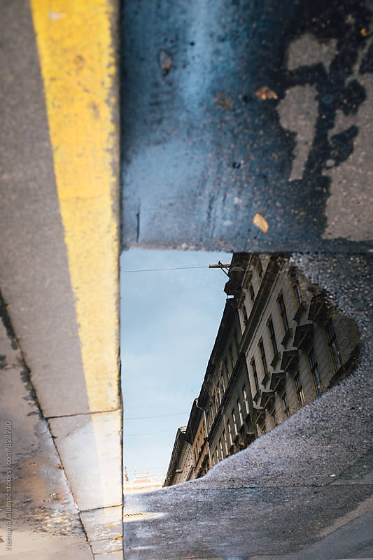Building Reflection in a Puddle in Budapest by Nemanja Glumac for Stocksy United
