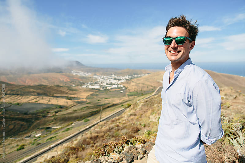 Happy traveler man with view of remote village in mountains by Alejandro Moreno de Carlos for Stocksy United