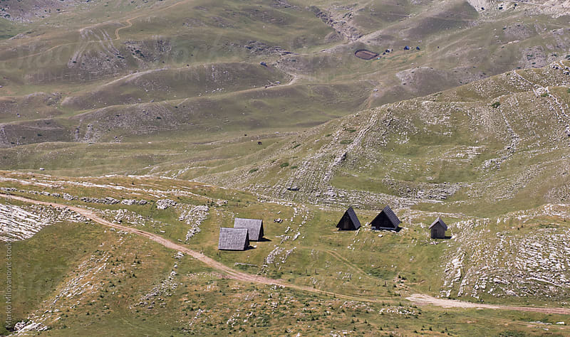 Serbian traditional houses in mountain meadow by Marko Milovanović for Stocksy United