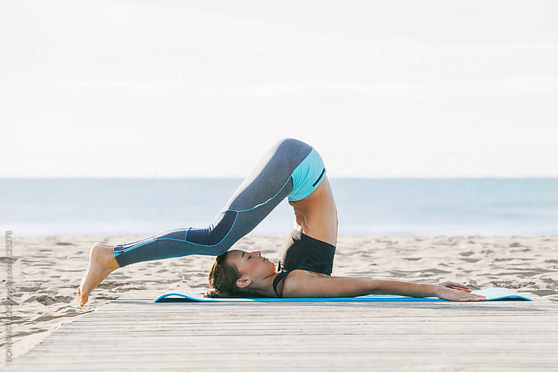 Young woman practicing yoga on the beach at sunset.  by BONNINSTUDIO for Stocksy United