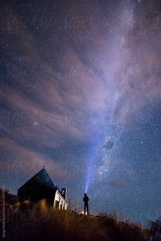 A male adventurer with strong headlamp beside Church of the Good Shepherd under the Galaxy by Song Heming for Stocksy United