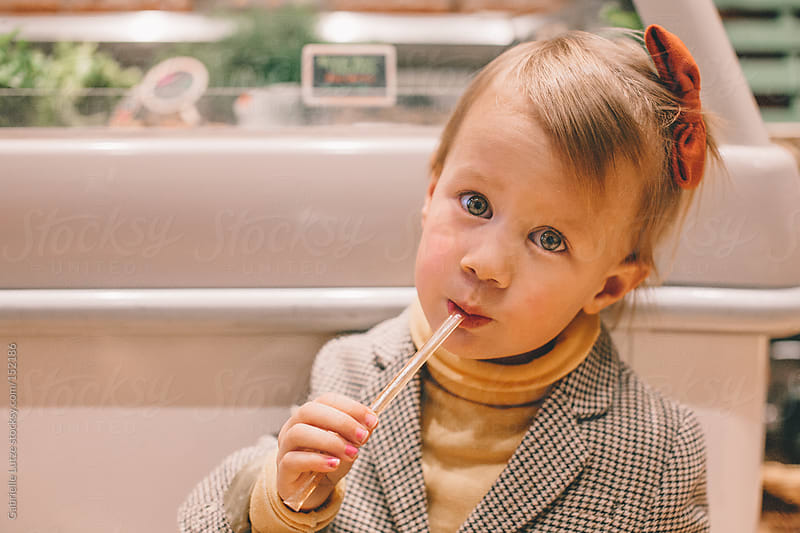 Little Girl with Honey Stick at Grocery Store  by Gabrielle Lutze for Stocksy United