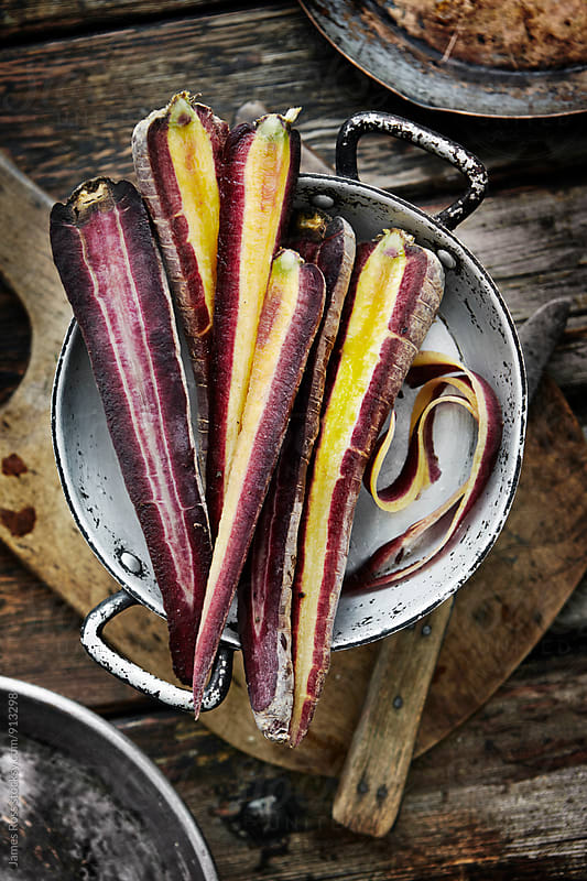 Cut purple carrots by James Ross for Stocksy United
