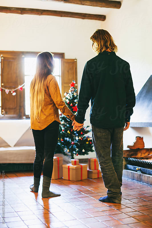Young couple celebrating Christmas in a rural home. by BONNINSTUDIO for Stocksy United