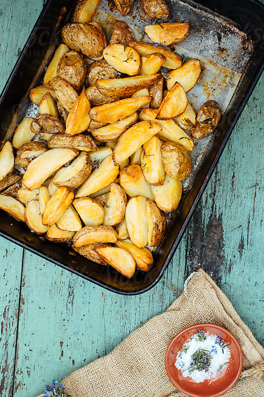 roasted potato dishes in the baking tray, with rosemary and salt garnish by Gillian Vann for Stocksy United