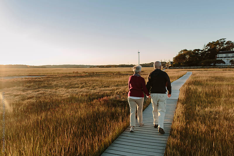 Couple on Boardwalk in Autumn by Raymond Forbes LLC for Stocksy United