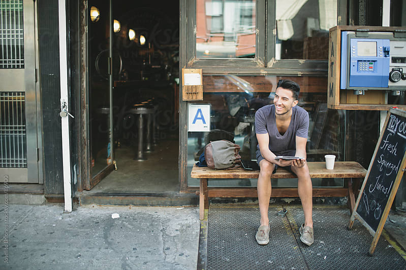 Hip Young Man Using Tablet Device Sitting Outside a Cafe by Joselito Briones for Stocksy United